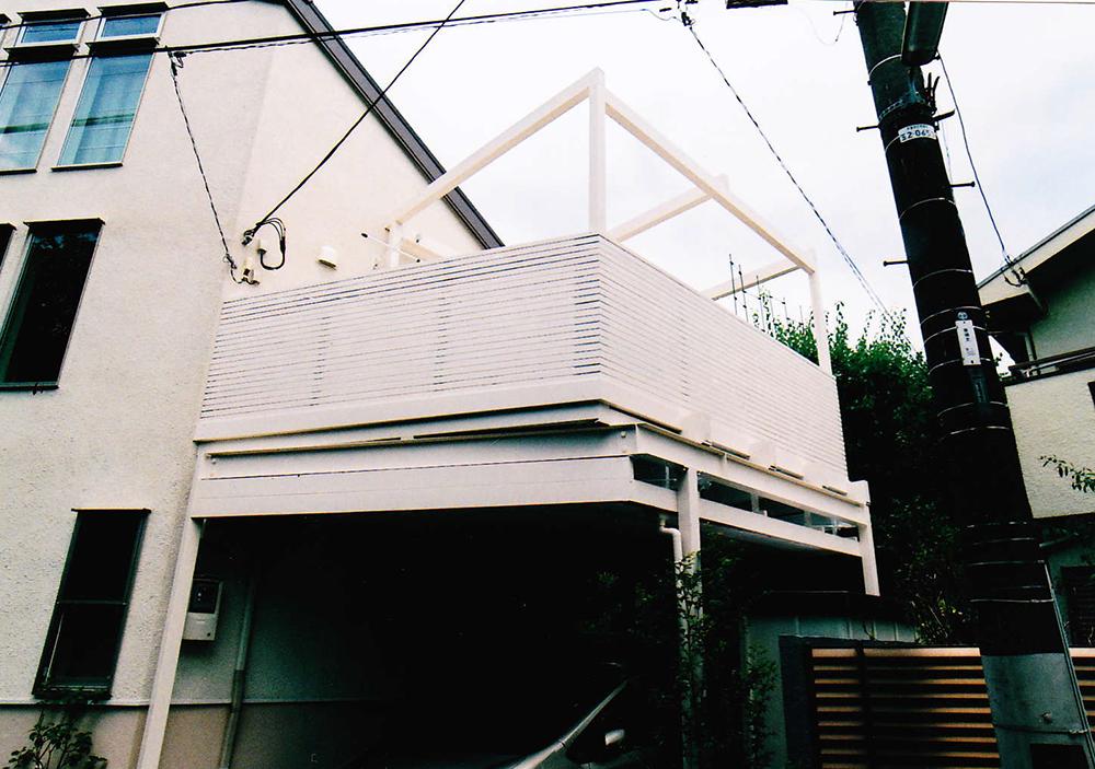 東京都世田谷区N様邸 鉄骨架台のウッドバルコニー。がっしりとしたパーゴラと街並みにとけこむ白いデッキがポイント